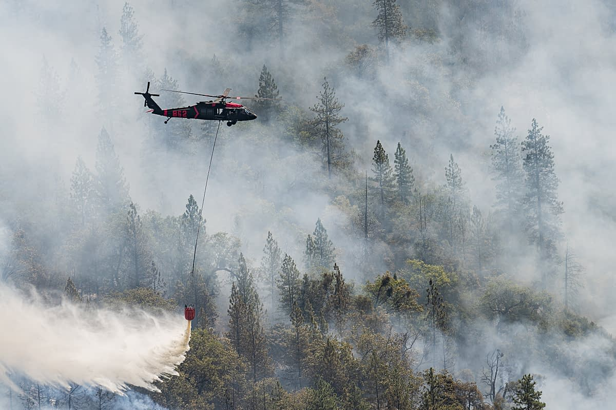 Helicopters work continually throughout the day dropping water on a hot zone that erupted near the fire decimated town of Grizzly Flats. California, USA, 2021. Nikki Ritcher / We Animals Media