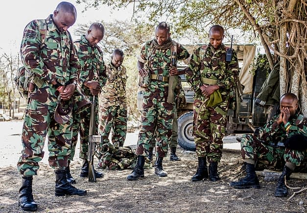 NPR (National Police Reservists) have a moment of prayer before they go out on an overnight patrol of Ol Pejeta Conservancy in Central Kenya. The armed men patrol the 360 km2 (140 sq mi) not-for-profit wildlife conservancy around the clock and protect the rhinos and other animals from deadly poachers. Kenya, 2019. Justin Mott / Kindred Guardians Project / We Animals Media
